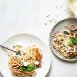 two plates of summer spaghetti with glasses of white wine