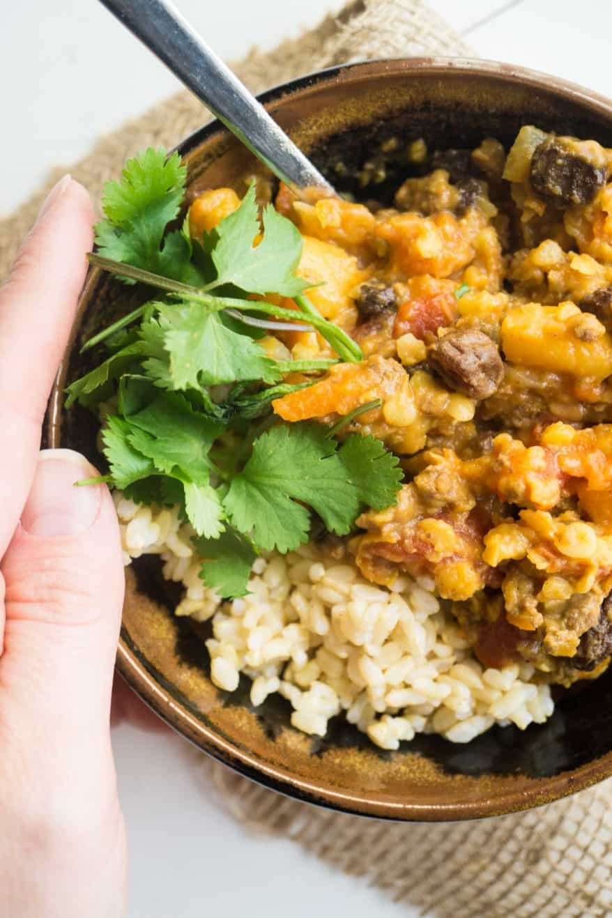 Moroccan Beef and Lentil Bowl with parsley garnish and rice. A hand holding the side of the bowl