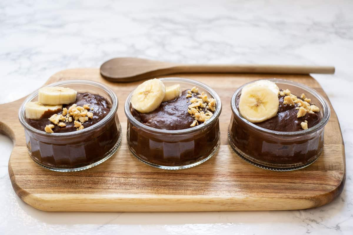 3 small bowls of chocolate pudding on a wooden board topped with sliced bananas and chopped peanuts