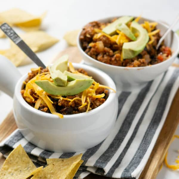two bowls of turkey quinoa chili surrounded by tortilla chips and half an avocado in the background