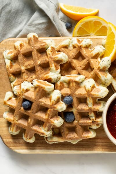 platter of orange poppyseed protein waffles with a bowl of strawberry sauce