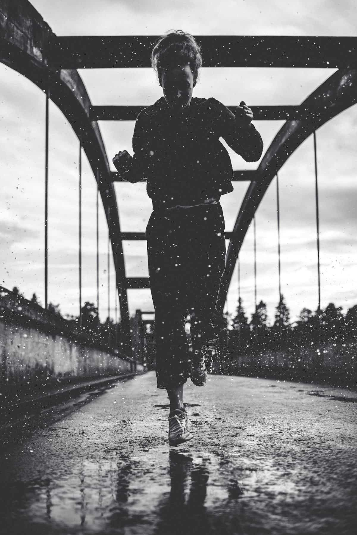black-and-white-photo-of-woman-running-on-bridge-in-the-rain