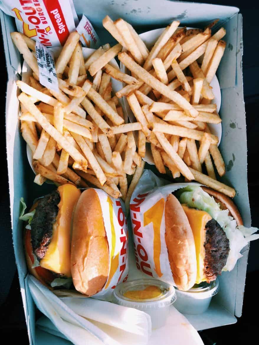 A flay lay photo of two bags of fries and two cheeseburgers.
