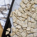 Baking sheet filled with homemade sourdough crackers with flax and chia seeds
