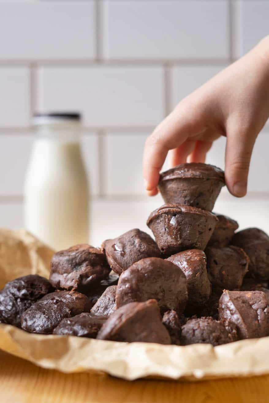 A pile of two bite protein brownies with a hand reaching for the top brownie and a bottle of milk in the background