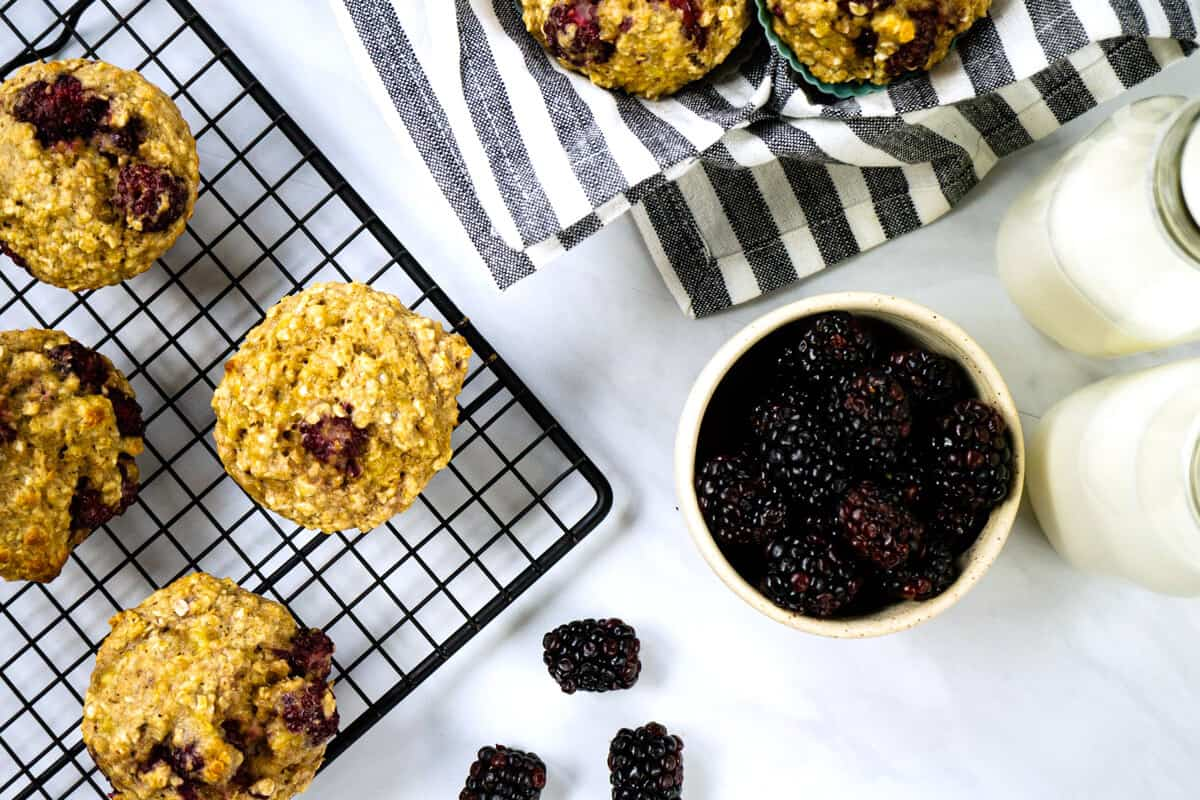 overhead view of blackberry oatmeal muffins cooling on a rack beside a bowl of fresh blackberries and two glass jars of milk