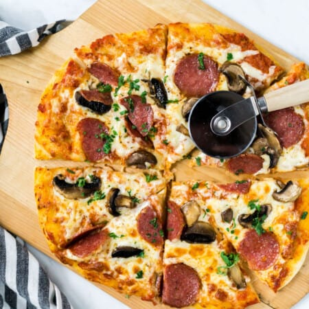a baked and sliced sourdough pizza topped with salami and mushrooms lying on a pizza peel with a pizza slicer