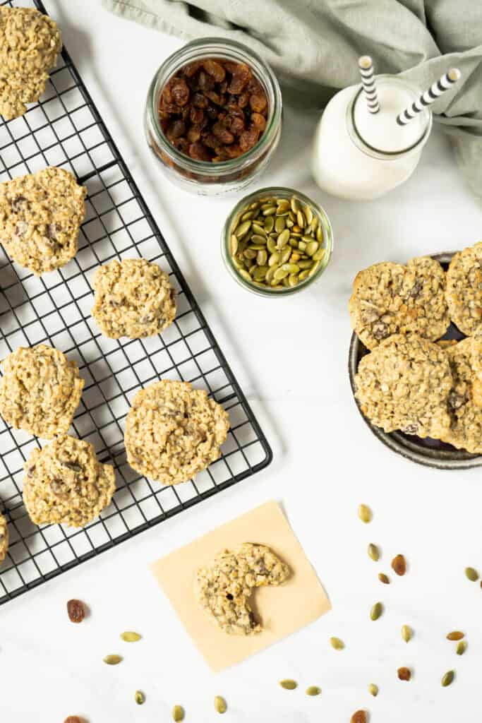 Birds eye view of trail mix cookies on a cooling rack and on a plate with a jug of milk.