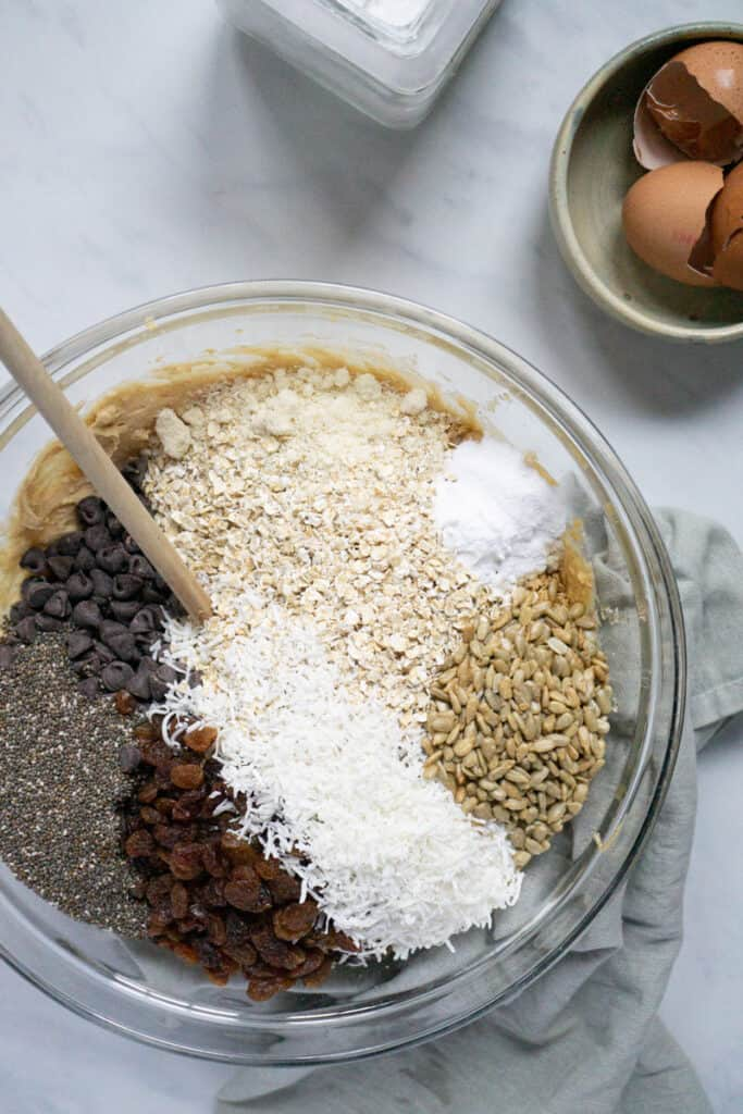 Ingredient for trailmix cookies in a mixing bowl.